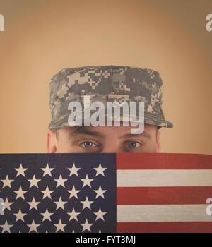 Un soldat de l'armée militaire est maintenant un drapeau américain jusqu'à son visage avec un uniforme sur et copyspace pour un ancien combattant, memorial ou il