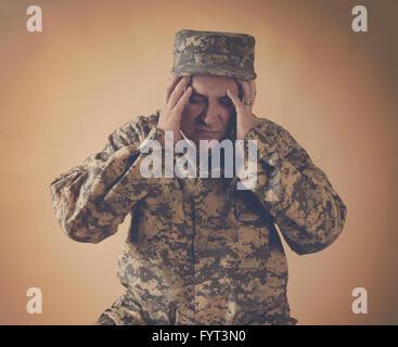 Un homme de l'armée a souligné tient ses mains à sa tête sur un arrière-plan pour un effet de guerre ou douleur Banque D'Images