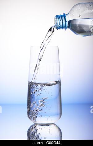 Verser de l'eau en bouteille en plastique à moitié rempli de boire dans un verre avec réflexion sur fond bleu et Banque D'Images