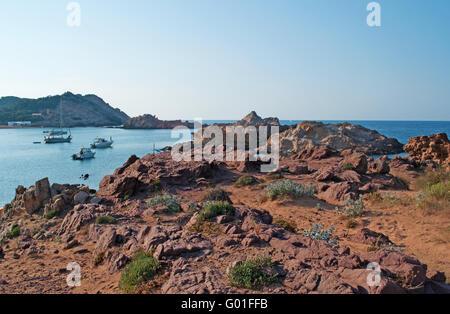 Menorca: sable rouge sur la voie de la Cala Pregonda, baie isolée avec des pierres et du sable rouge: sa plage Banque D'Images