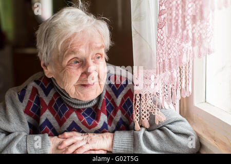 Une femme âgée, une grand-mère, avec un sourire en regardant par la fenêtre assis dans la cuisine. Banque D'Images