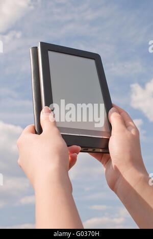 Mains tiennent le lecteur de livres électroniques contre le ciel bleu Banque D'Images