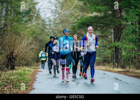 Groupe de jeunes filles athlètes exécutant le long de la route au cours de semi-marathon en bois Banque D'Images