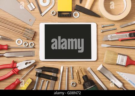 Écran tactile numérique bannière avec tous les outils de bricolage et de travail autour d'une table en bois, vue Banque D'Images