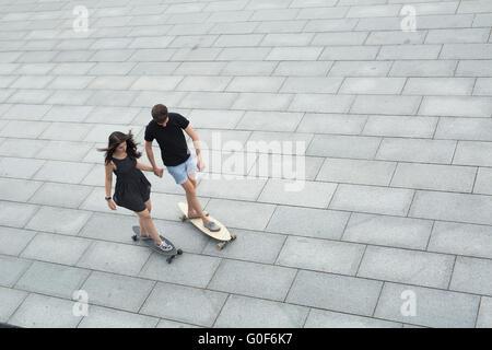Les jeunes adolescents élégante paire de longboards ride Banque D'Images