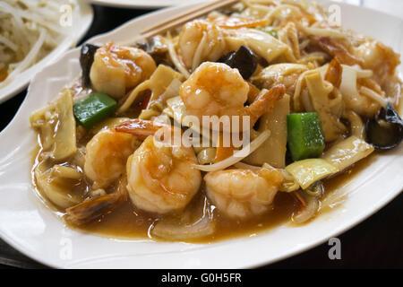 La cuisine chinoise - faire revenir les crevettes avec légumes et champignons. Banque D'Images