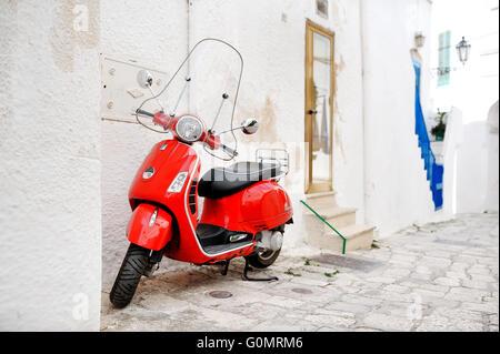Scooter italien vespa rouge dans une ruelle, Ostuni, Pouilles, Italie méditerranée Banque D'Images