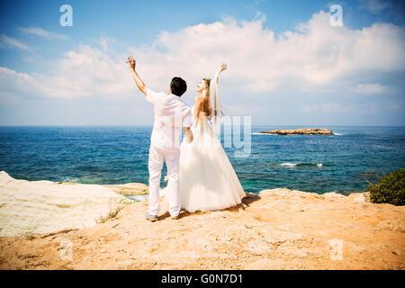 Mariée et le marié élégant la marche sur la plage, cérémonie de mariage, Mer Méditerranée. Banque D'Images