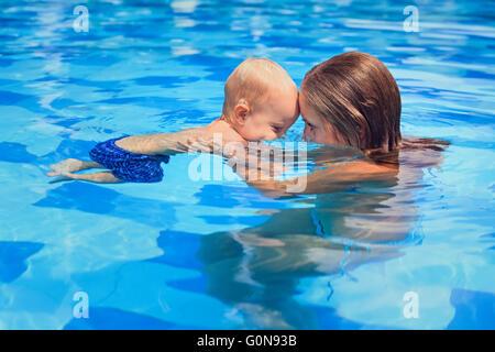 Little man sports avec la mère - nager avec bébé active in femme mains dans la piscine. Banque D'Images