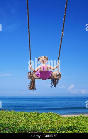Little baby girl voler haut avec plaisir sur rope swing sur fond de ciel bleu sur la plage de la mer avec des vagues Banque D'Images