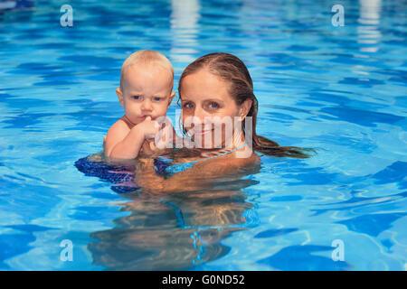 Little man sports a leçon de natation avec la mère - nager avec bébé active in femme mains dans la piscine. Banque D'Images
