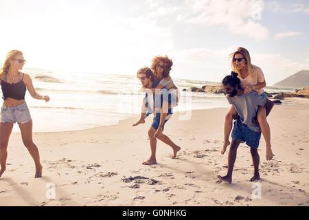 Groupe d'amis s'amusant sur la plage vacances, les hommes sur le dos des femmes. Banque D'Images