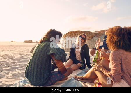 Portrait of young man playing guitar for friends. Groupe d'amis s'amuser à la plage de travail. Les jeunes hommes et femmes assis sur