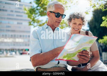 A Senior couple plan de la ville. Homme mature et femme assise à l'extérieur de la ville dans la lecture d'un site pour l'orientation.