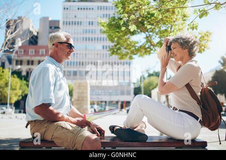 Vue latérale du senior à l'extérieur sur un banc et la femme en tenant ses photos avec l'appareil photo numérique. Banque D'Images