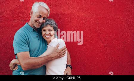Portrait of mature affectueux couple contre fond rouge et souriants. Senior couple contre mur rouge w Banque D'Images