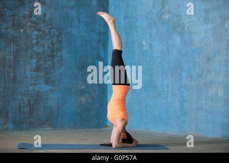 Belle jeune femme vêtue de vêtements de yoga à l'intérieur. Yogi girl working out in grunge mur bleu avec intérieur Banque D'Images