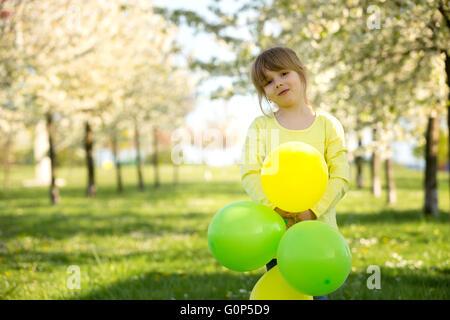 Cute little girl Playing with balloons dans un jardin en fleurs pommier, en fin d'après-midi ensoleillée de printemps Banque D'Images