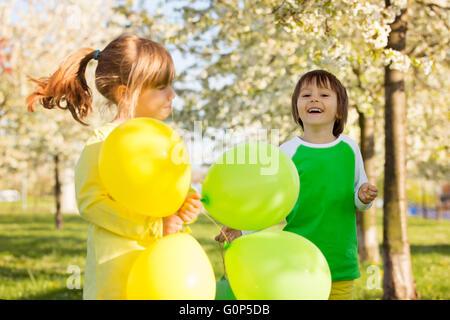 Cute little girl and boy, amis, jouer avec des ballons dans un jardin en fleurs pommier, en fin d'après-midi ensoleillée Banque D'Images