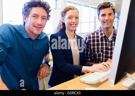 Businesspeople smiling et posant devant un ordinateur