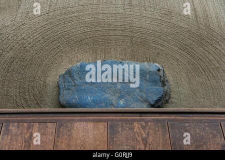 Une vue détaillée montre une chaussure-retrait de pierre dans le sable ratissé avec soin sous la véranda engawa Banque D'Images