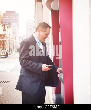 Un homme d'affaires est maintenant un téléphone et retirer de l'argent de son compte à un guichet automatique pour un centre-ville finances o