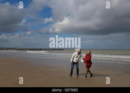 Heureux l'homme et la femme se tenant la main et messing sur sur la plage, Knokke, Belgique Banque D'Images