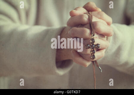 Senior woman with hands clasped tenant un crucifix