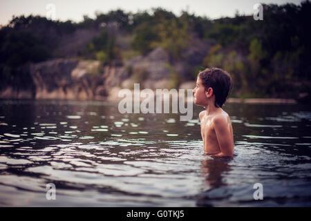 Garçon debout dans le lac au coucher du soleil, le Texas, l'Amérique, USA Banque D'Images