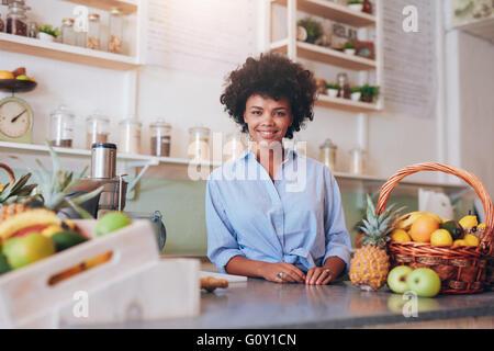 Portrait de belle jeune femme debout au comptoir dans un bar à jus souriant pour appareil photo. Femme africaine Banque D'Images