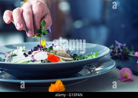 Chef de l'établissement hotel ou restaurant Cuisine Cuisine, seulement les mains. Il travaille sur l'herbe micro Banque D'Images