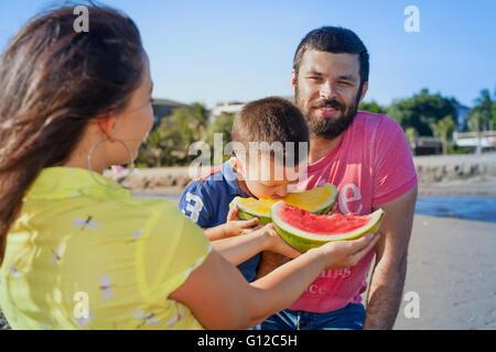 Drôle de famille heureuse pique-nique sur une plage de la mer du matin - mère nourrir bébé garçon, homme adulte. Banque D'Images