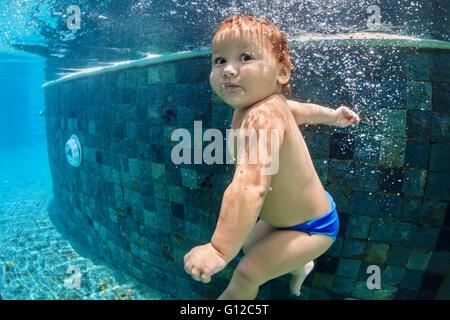 Funny photo de bébé active la natation et la plongée en piscine avec plaisir - aller au fond avec des touches sous Banque D'Images