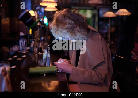 Le dirigeant d'une femme israélienne à partir de la Russie à l'aide de son téléphone portable en Poutine bar nommé Banque D'Images
