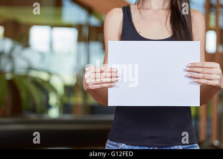 Young caucasian woman holding feuille de papier blanc Banque D'Images