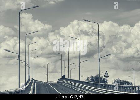 Route de l'autoroute interstate vide avec lampadaires plus de nuages dans le ciel. Monochrome, noir et blanc. Banque D'Images