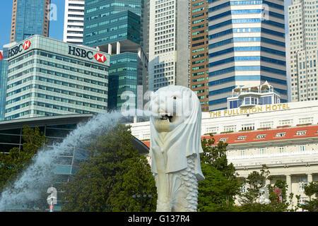 Le Merlion Fontaine avec Fullerton Hotel de luxe et le quartier des affaires de Singapour derrière l'horizon.