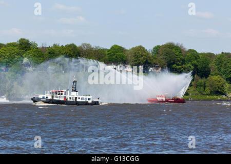 Bateau sur l'elbe pulvériser de l'eau au départ défilé de 827e anniversaire du port de Hambourg, le vieux bateau Banque D'Images