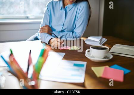 Femme propriétaire de petite entreprise travail à la maison assise à son bureau en prenant des notes sur des cartes Banque D'Images