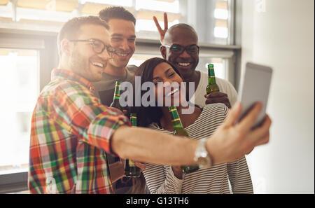 Amis au travail taking self portrait with camera phone tout en maintenant des bouteilles de bière en verre vert Banque D'Images