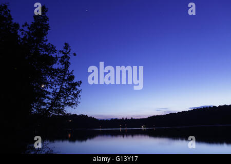 Paysage de nuit sur un lac de l'Ouest Vermont à avec Star Trails et une longue traînée de lumière à partir de la Banque D'Images