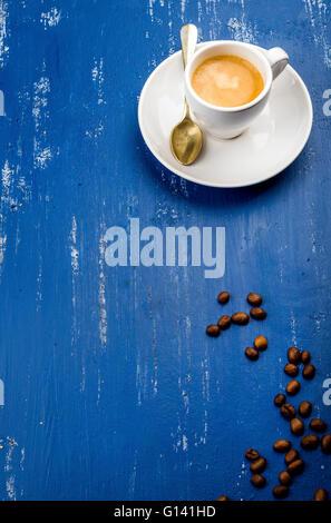 Tasse de café espresso et de haricots sur la table en bois peint bleu arrière-plan. Vue d'en haut, vertical Banque D'Images