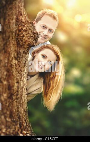 Happy young couple standing behind tree et d'avoir du plaisir Banque D'Images
