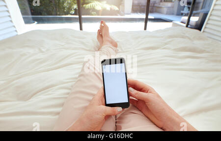 Libre de droit de woman lying on a bed holding a smart phone avec écran vide. POV shot of woman relaxing in coucher Banque D'Images
