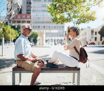 Vue latérale d'homme mûr assis sur un banc et la femme de prendre ses photos avec un appareil photo numérique. Surfers Banque D'Images