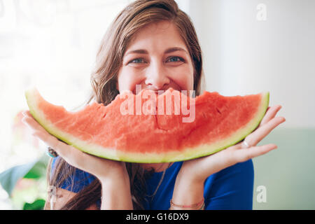 Portrait of happy young woman holding une tranche de melon d'en face de son visage. Banque D'Images