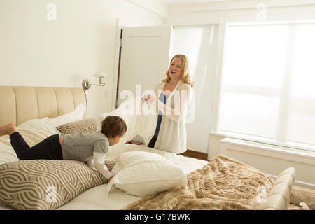 Woman making bed tout petit garçon jouant Banque D'Images