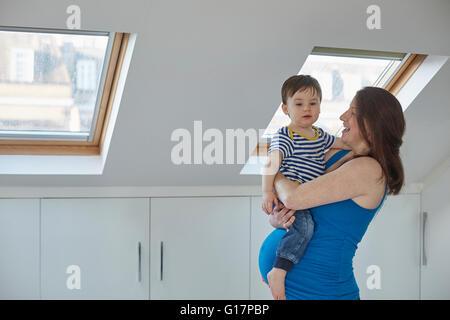 Vue du côté des femmes enceintes mother holding baby boy Banque D'Images