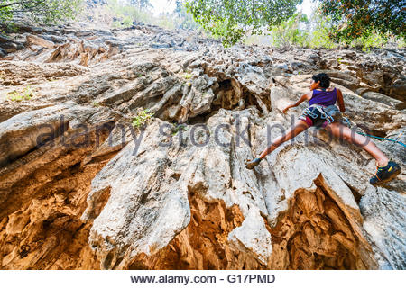Low angle view of young woman escalade rocher, Thakhek, Khammouane, Laos Banque D'Images