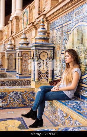 Jeune femme assise à la Plaza de España, Séville, Andalousie, Espagne Banque D'Images